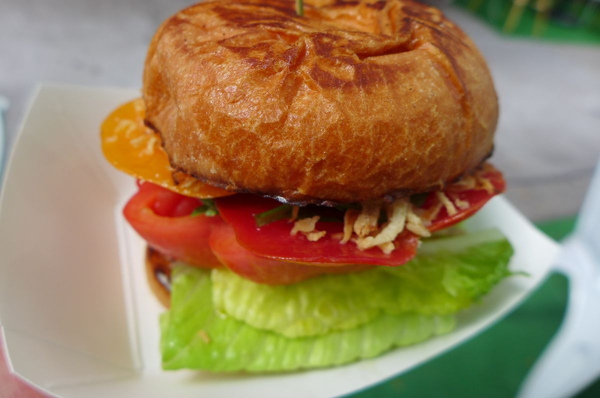 A tomato sandwich on a bun with red and yellow tomatoes sticking out and also light green romaine lettuce.