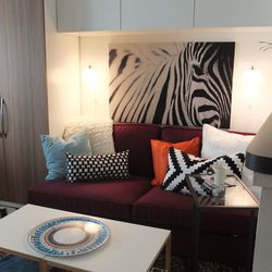 The whole apartment is a cheerful mix of colors and patterns, which Mansaray loves. The units above the sofa are BESTA units with BESTA VARA doors. The lights above the sofa are MINUT. The tables in the entertaining area are IKEA PS, and VITTSJO laptop st