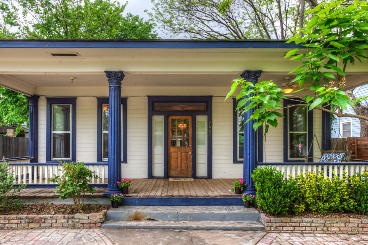One story wood frame house with big, wide covered front porch, painted white with dark blue columns and trim