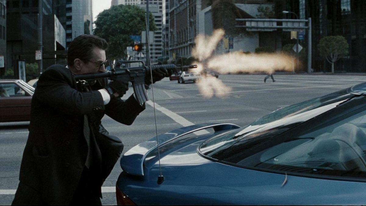 Robert De Niro fires a rifle on the street in Heat