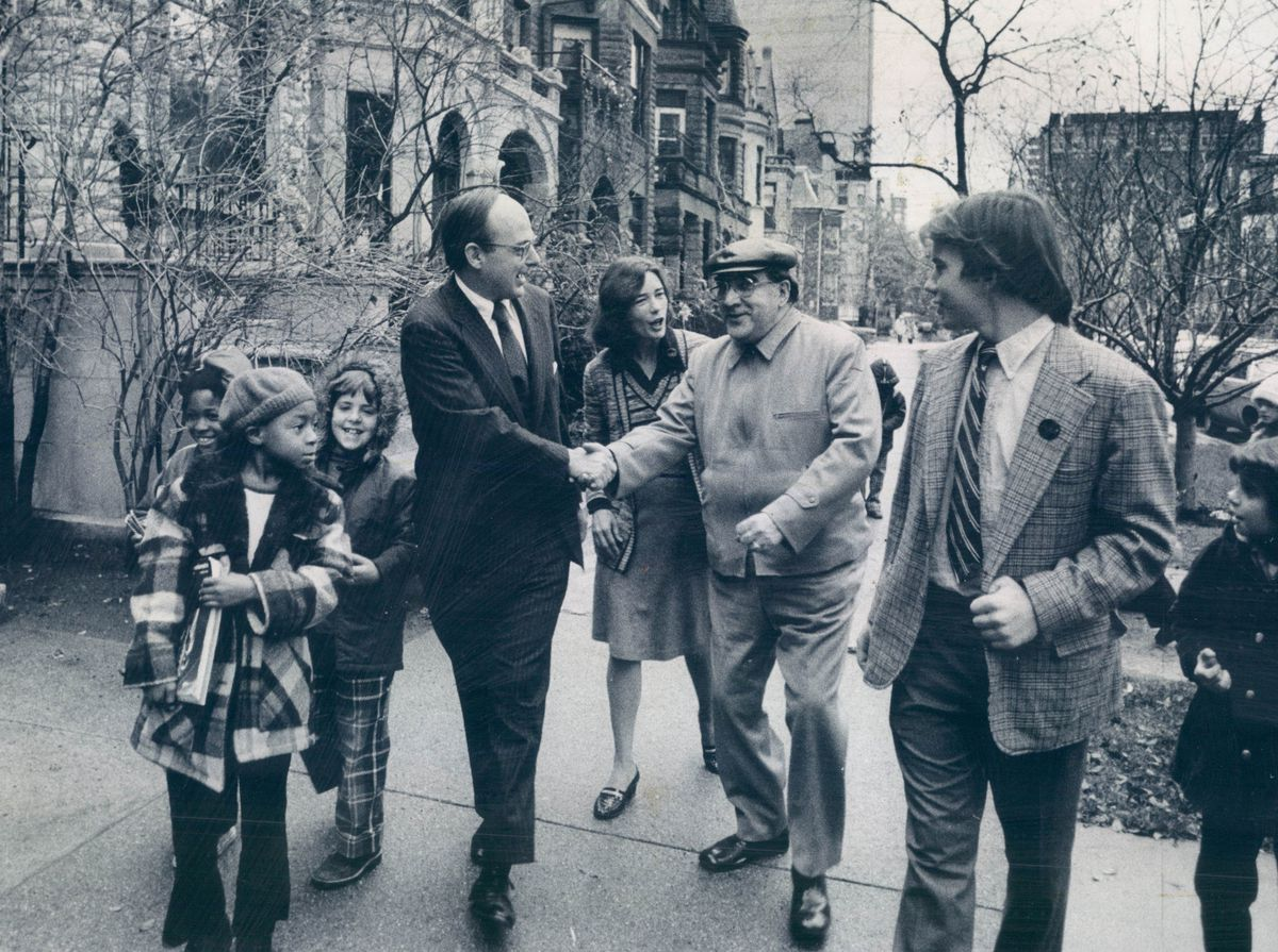 On his way to the polling place in 1974, Sen. Adlai E. Stevenson III (is greeted by a well-wisher on North Dearborn. With the senator are his wife, Nancy, and son, Adlai IV, right, who voted for the first time that day.