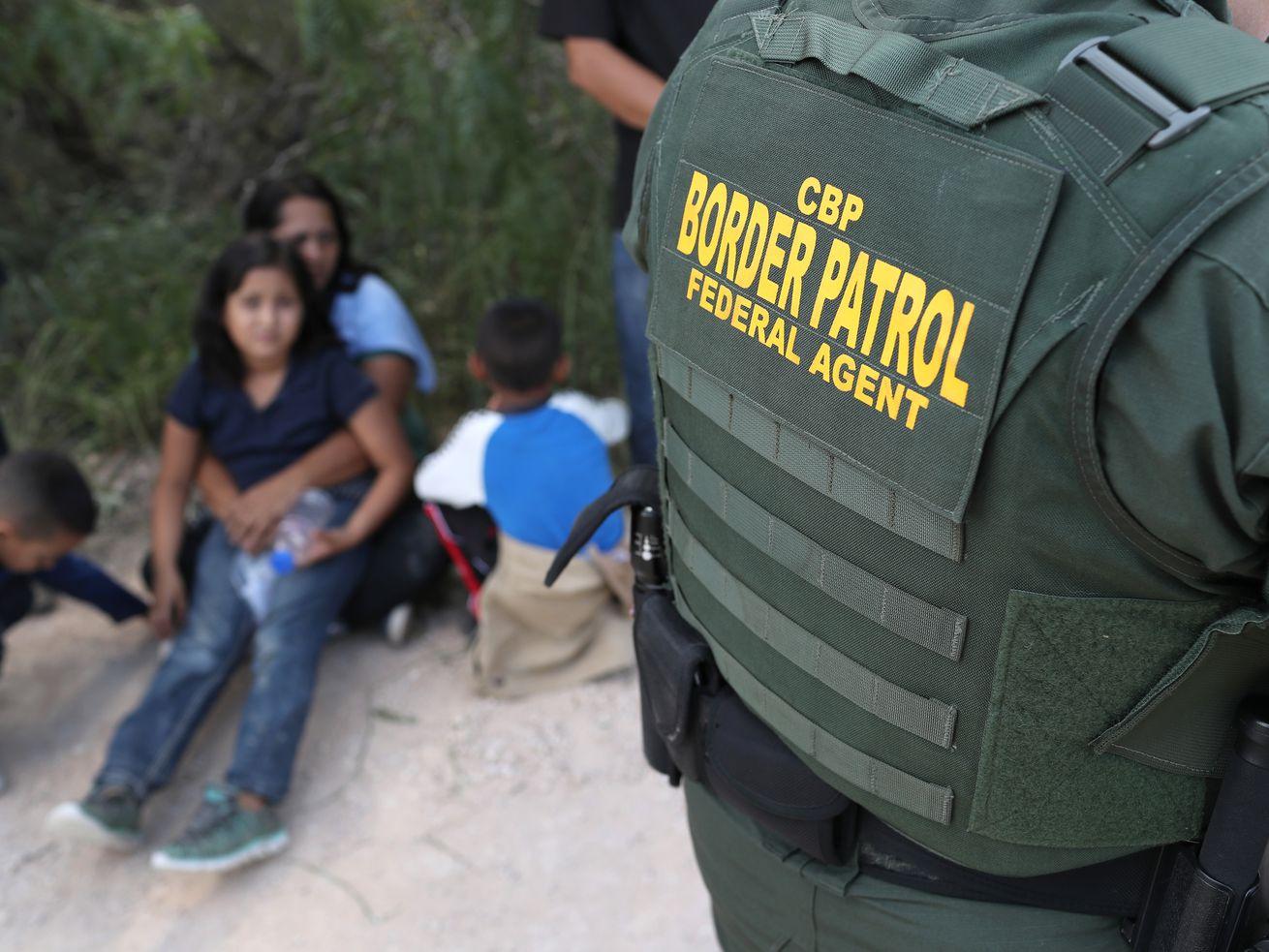 Central American asylum seekers wait as US Border Patrol agents take them into custody on June 12, 2018, near McAllen, Texas.