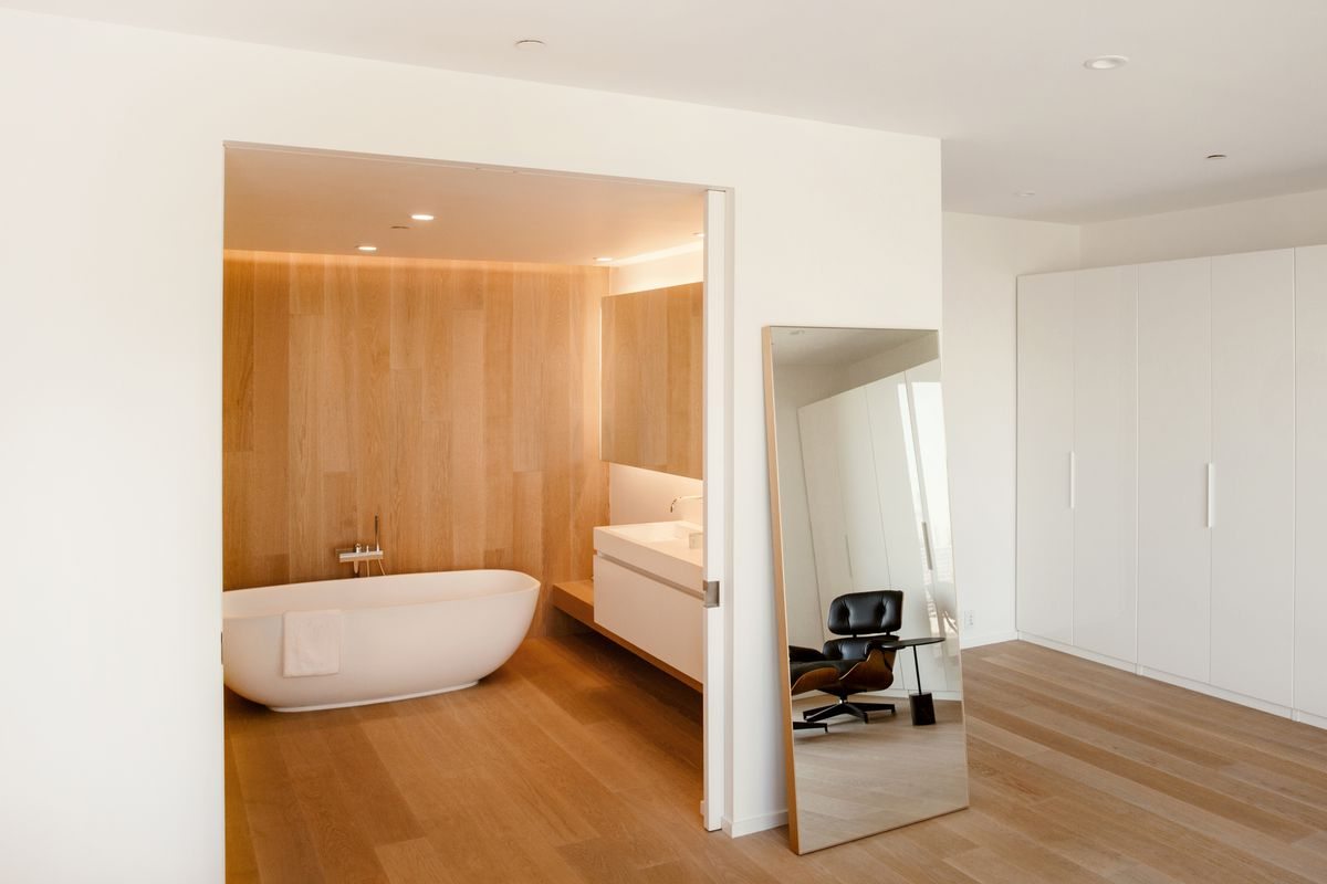 A bedroom with an opening to the bathroom, which contains a large white tub and white sink. A large floor mirror leans against the wall.