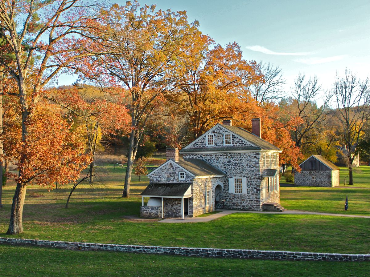 A historic stone house surrounded by trees with orange leaves.