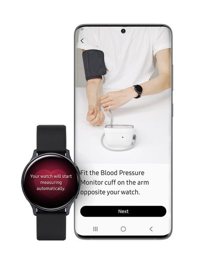 """A watch sits next to a phone in a photo illustration. The watch has an image of a heart, and text that says """"your watch will start measuring automatically"""" The phone displays a photo of a person wearing a white shirt. One of the person's arms has a watch, the other has a blood pressure cuff."""