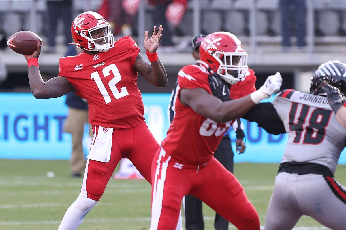 DC Defenders quarterback Cardale Jones passes the ball as NY Guardians linebacker Jawuan Johnson defends in the fourth quarter at Audi Field.