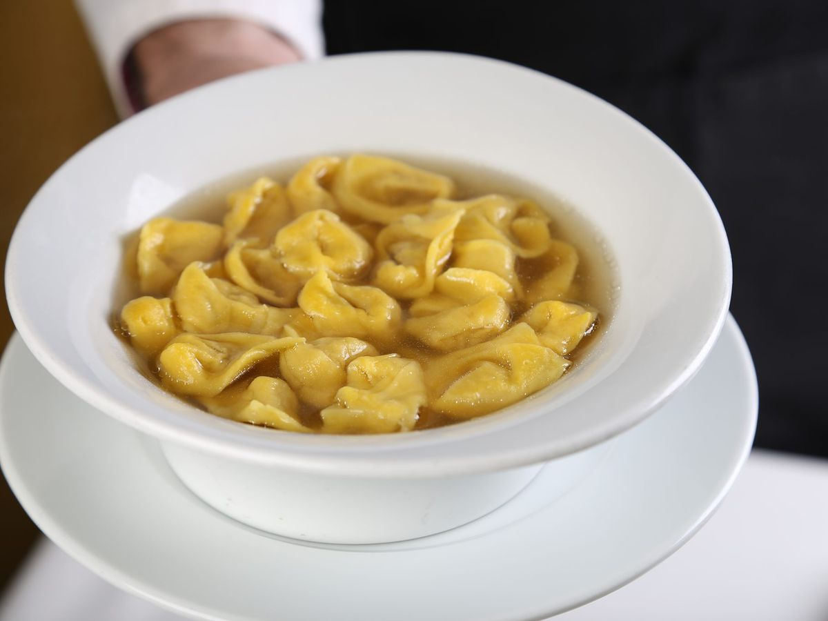 A server hands over a bowl of tortellini in broth on a saucer