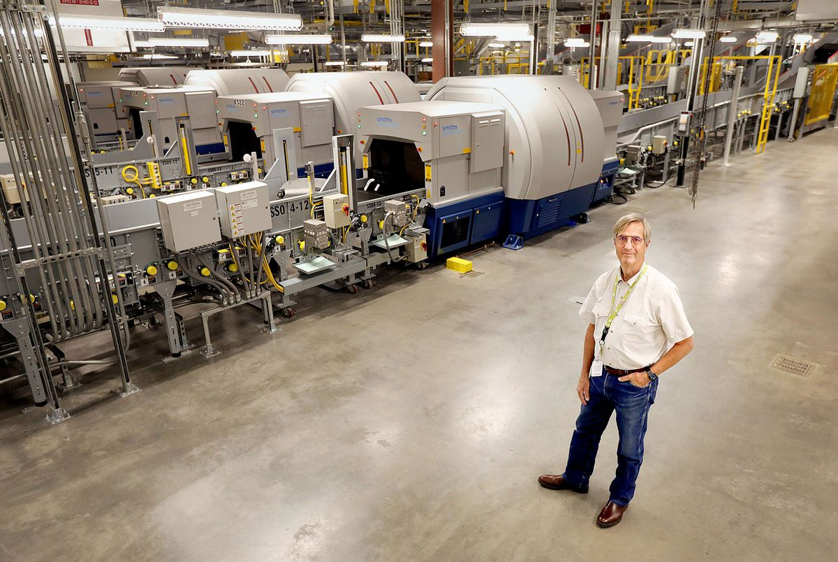 Bill Wyatt, director of the Salt Lake City International Airport, poses for a portrait near CT scanners that scan every checked bag at the airport in Salt Lake City on Thursday, Aug. 26, 2021.The scanners are part of increased security measures implemented after the 9/11 attacks.