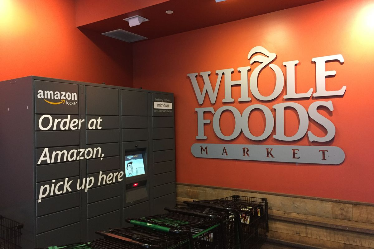 A black Amazon locker in front of an orange Whole Foods sign