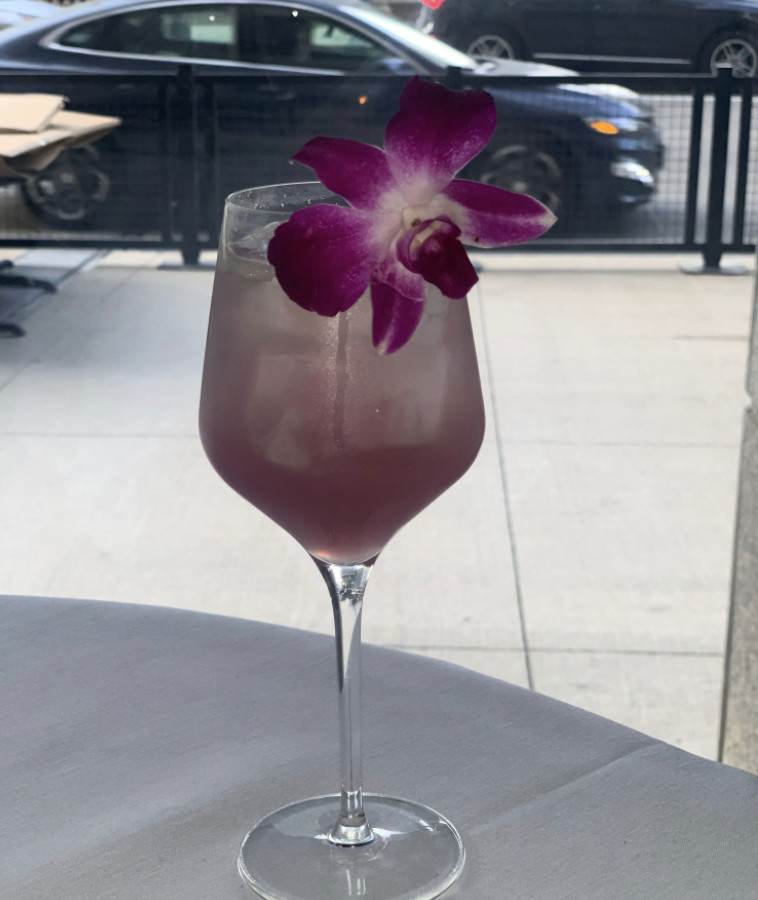 A cocktail in a wine glass topped with a purple orchid