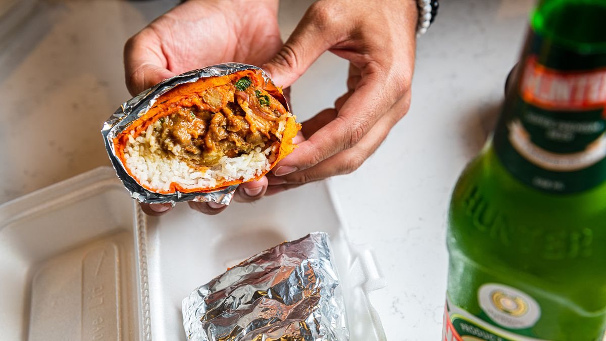A pair of hands displays a cross-section of a foil-wrapped veggie samosa burrito from Chit Chaat's gas station cafe.