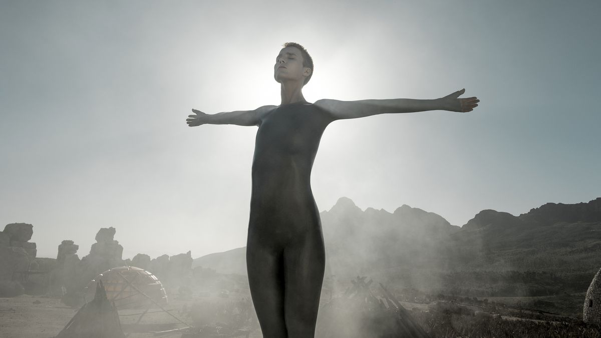 Amanda Collin stands with her arms out, silhouetted by the sun, in Raised By Wolves