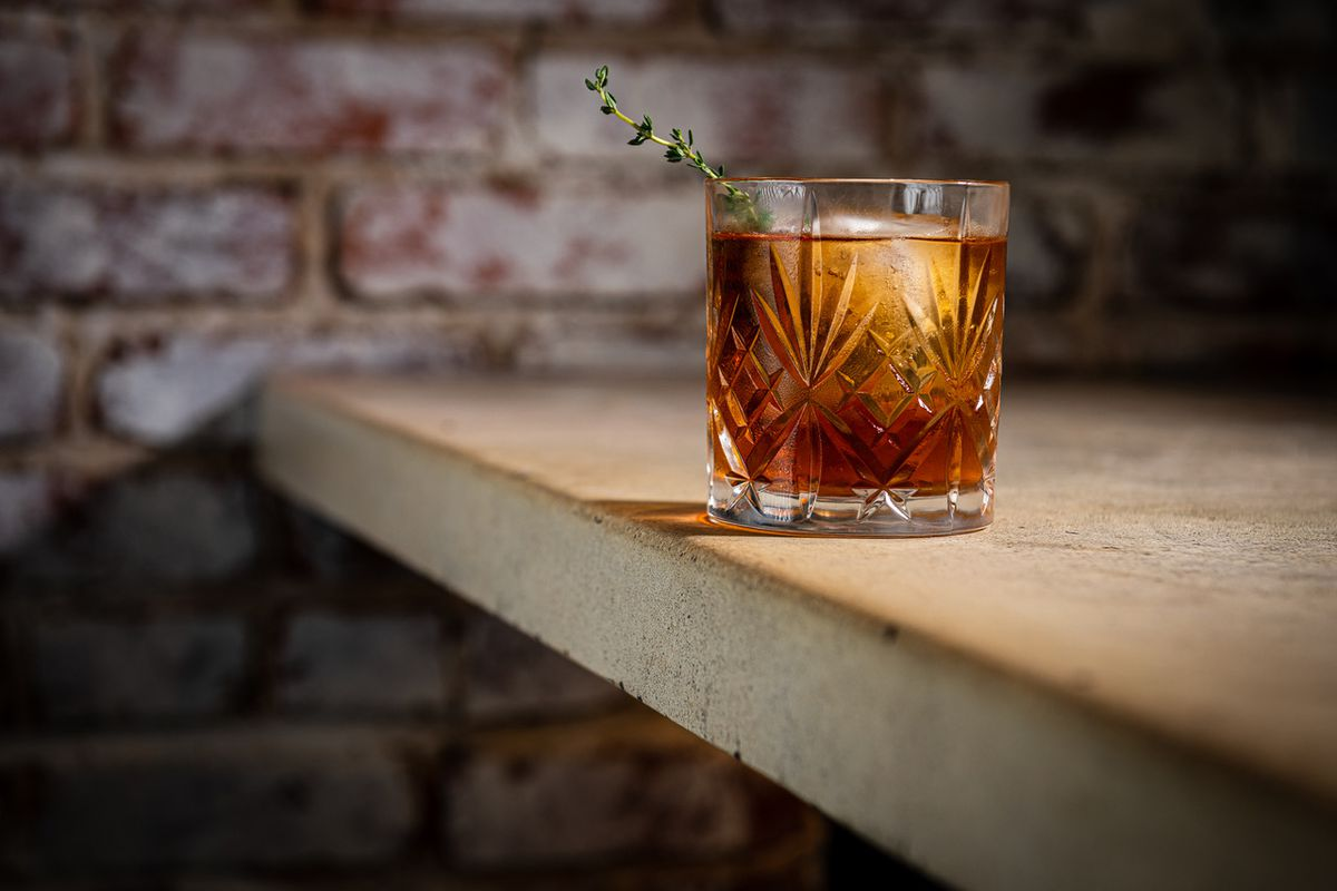 A Rob Roy from Bar Chinois contains sweet red vermouth infused with smoked black tea, Brenne single malt whisky aged in cognac casks, bitters, and a sprig of thyme.