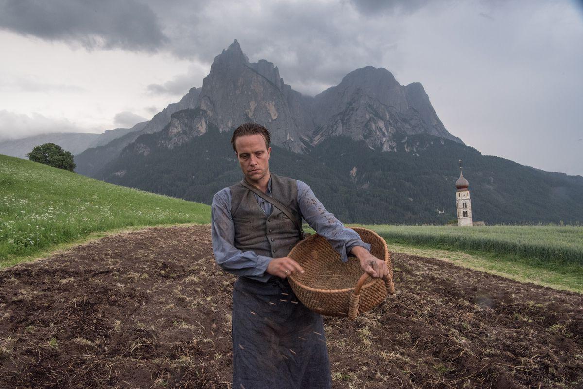 Franz Jägerstätter carries a wooden basket along a dirt field, a giant mountain popping through the clouds behind him
