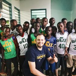 Zach Harding flashes a smile with a group of Ghanaian children wear donated Jr. Jazz jerseys at a learning center in Abomosu. The center was built previously by World Joy of Bountiful, Utah. A group of Utah humanitarians from MRIoA and World Joy did fun crafts with the kids, making clothespin airplanes and popsicle stick picture frames.