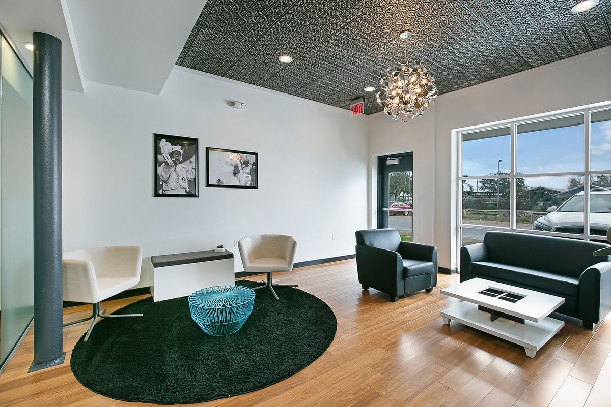 A large window overlooks a parking lot and illuminates a room with chairs, a sofa, white walls, and wood floors.