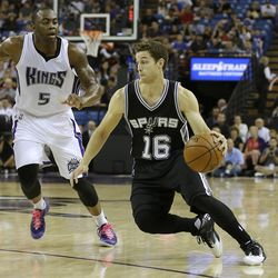 San Antonio Spurs guard Jimmer Fredette, right, drives against Sacramento Kings guard James Anderson during the second half of an NBA preseason basketball game in Sacramento, California, Thursday, Oct. 8, 2015.  The Kings won 95-92.