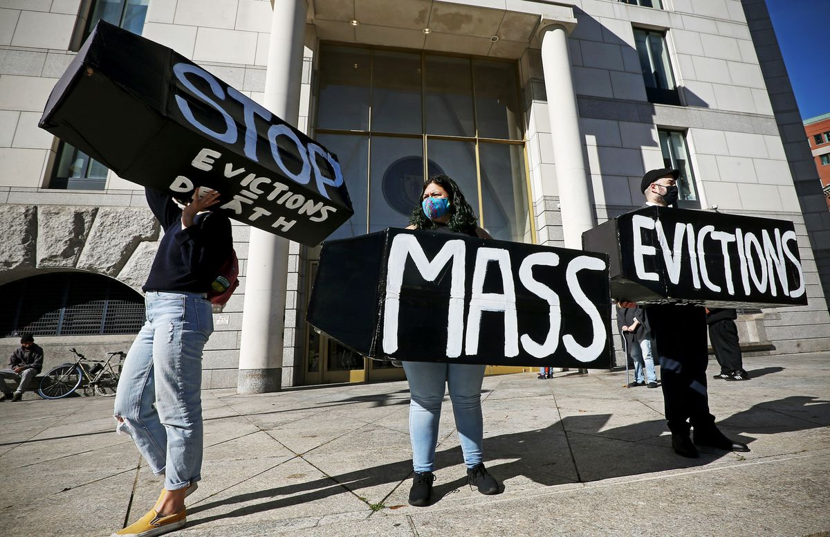 """Protesters outside a government building hold signs that read """"Stop mass evictions"""" and """"Evictions equal death."""""""