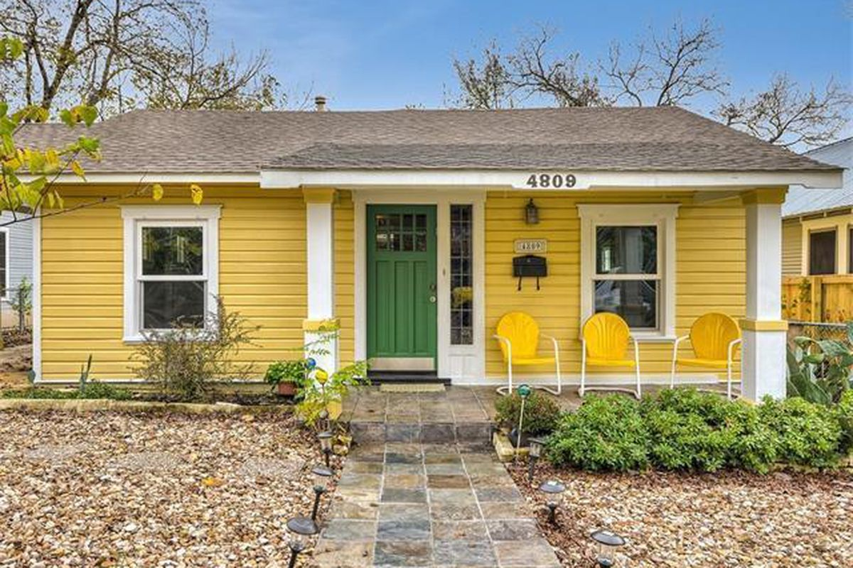 Bright yellow 1940s one-story wooden house