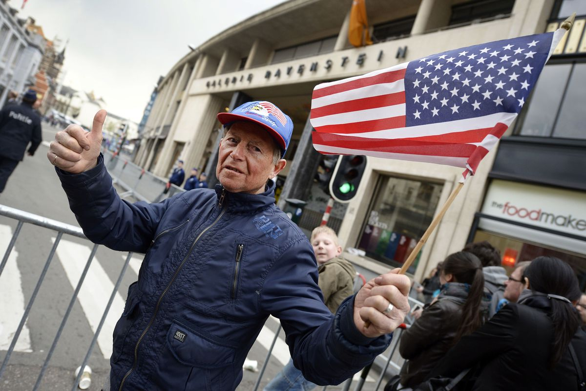 A man gives a thumb-up and waves a US flag as people gather outside the Palace of Fine Arts (BOZAR) in Brussels before the visit of the US president on March 26, 2014
