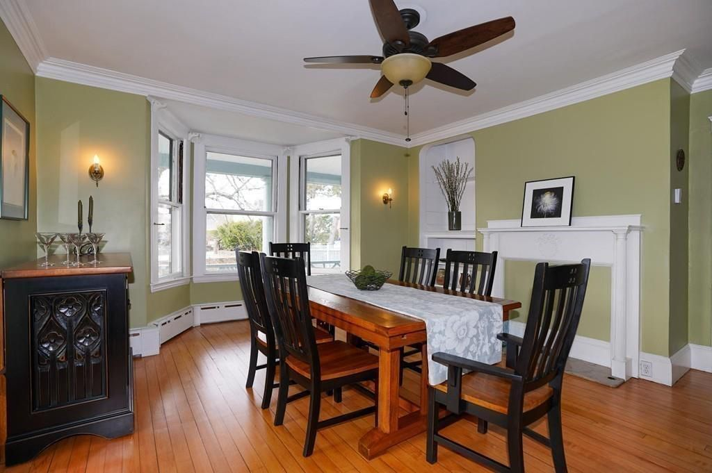 A dining room with a table and chairs and a filled-in fireplace.