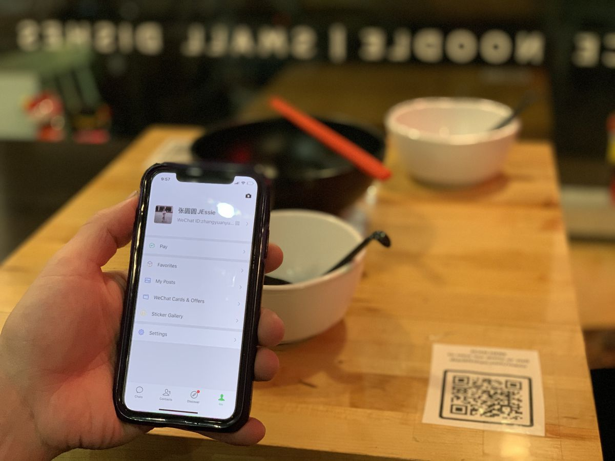 A phone being held up in front of a table with a QR code on the side