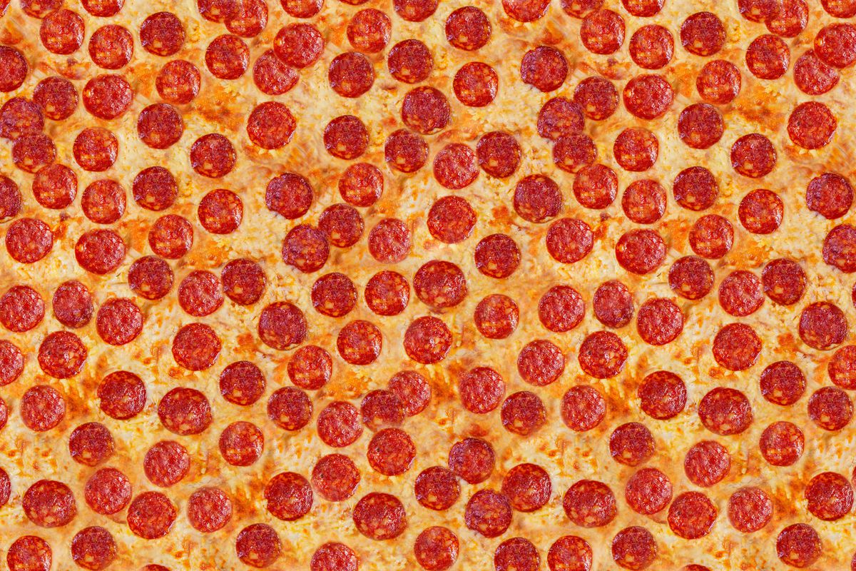 An overhead photo showing pepperoni slices scattered over melted cheese. There is no visible pizza crust.