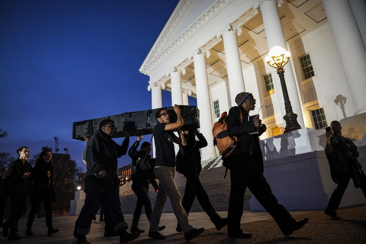 Protestors carry a fake coffin, to symbolize what they call the death of the Democratic Party, toward the Virginia State Capitol, on February 7, 2019 in Richmond, Virginia.