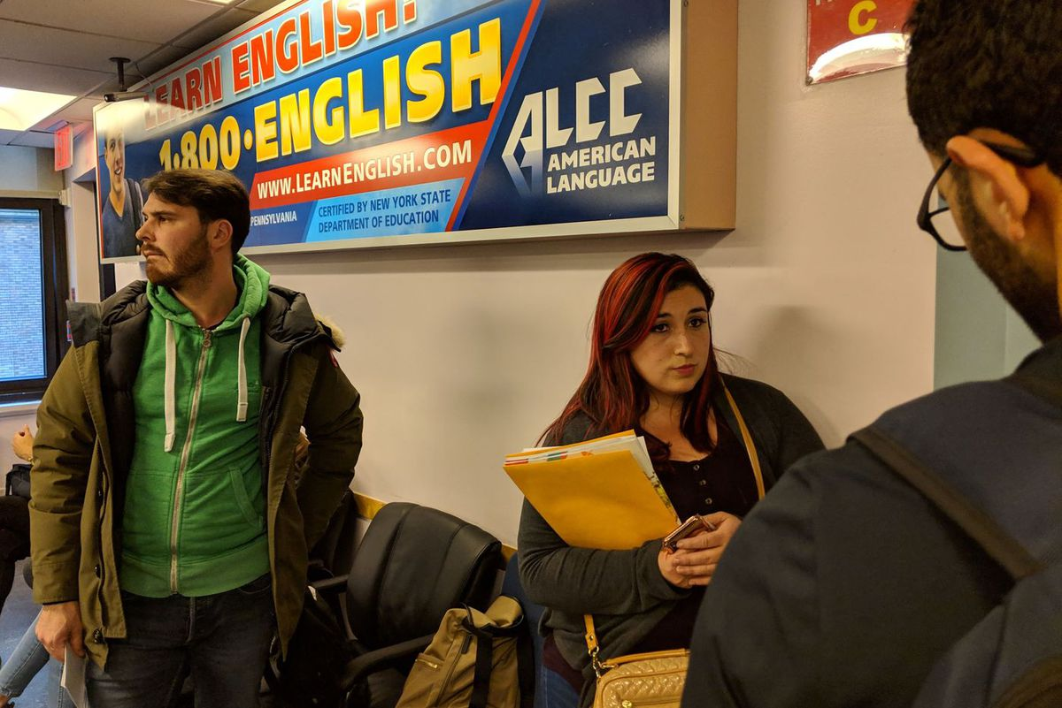 Florian Lobermayer, 28, of France (left) and Maribel Alanso, 28, of Colombia (right) wait in the ALCC office for information about the abrupt closure of the English language school.