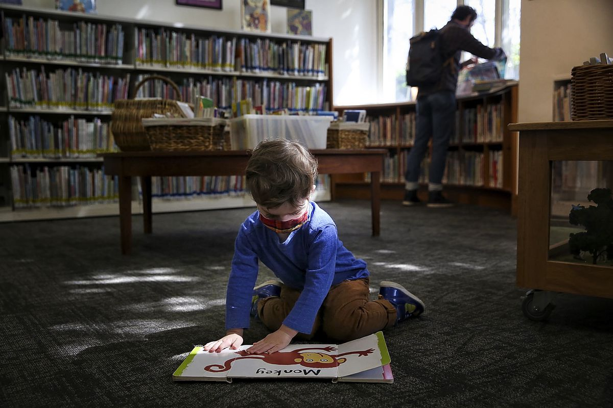 A toddler flips through a book on the ground in a library.