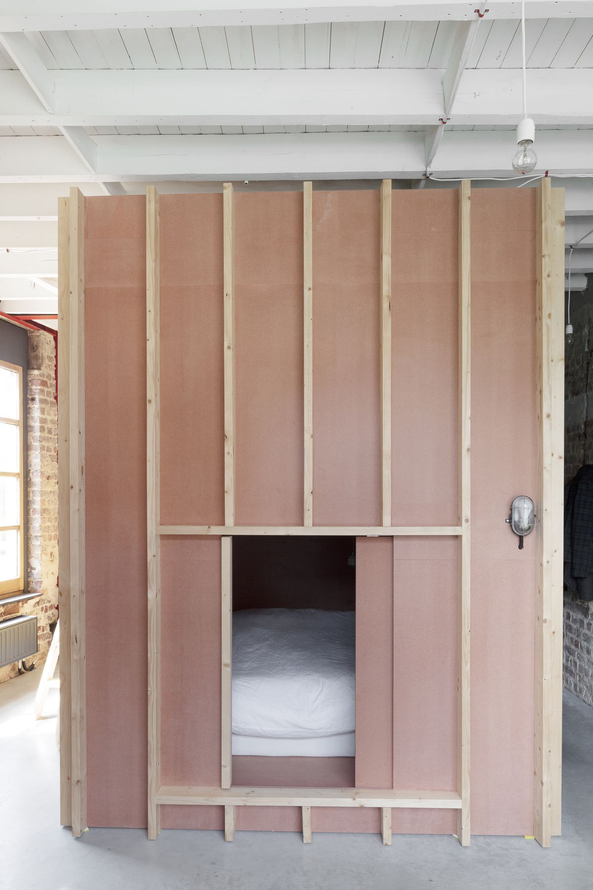 A wooden free standing room that has a bed nestled inside. The exterior is wooden. The floor is grey concrete.