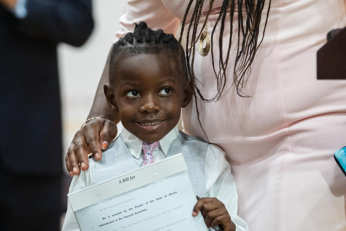 Jett Hawkins holds the bill that was just signed by Gov. J.B. Pritzker at Uplift Community High School in the Uptown neighborhood on Friday.