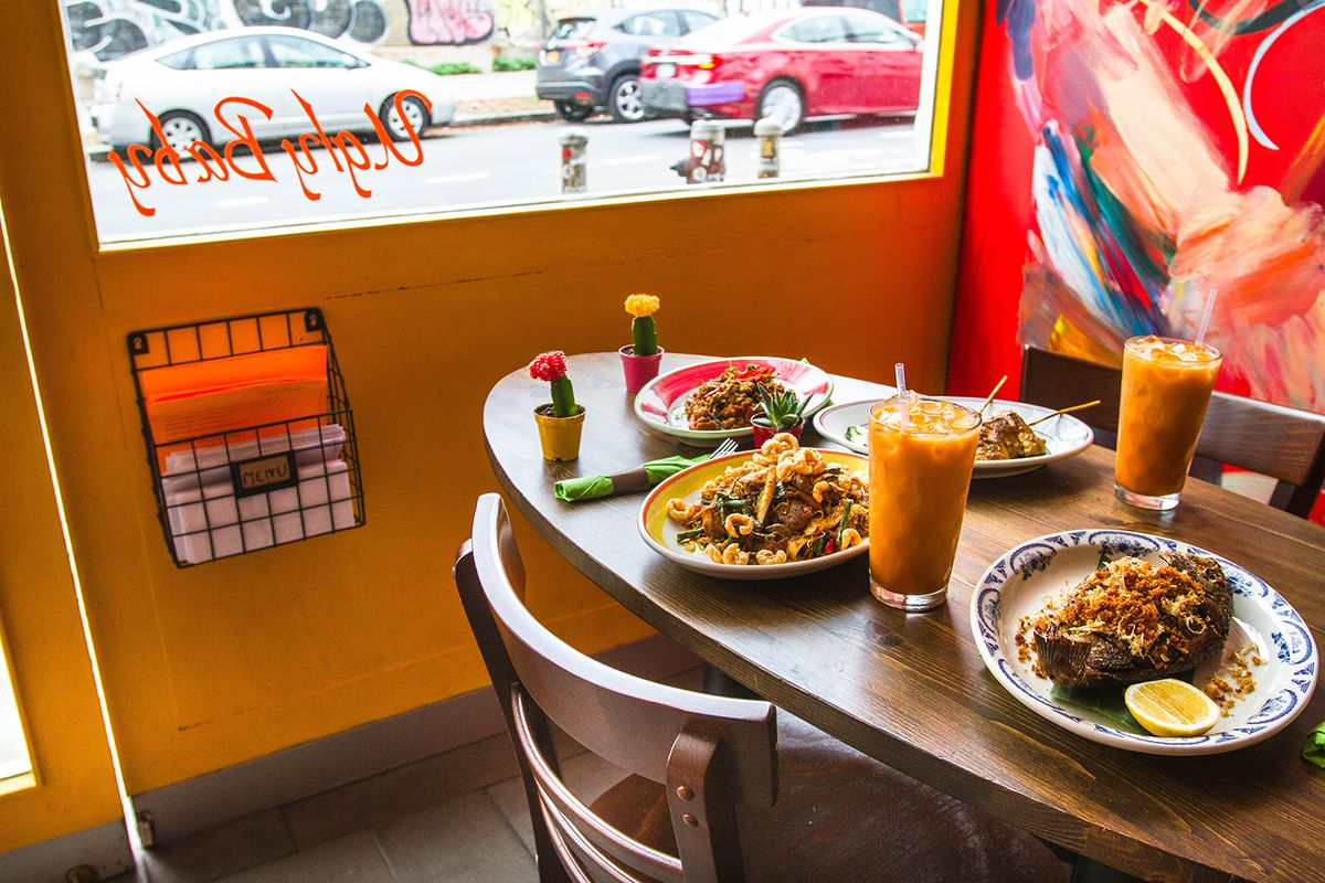 A dining table with several dishes, two orange drinks with ice cubes and a few decorative, palm-sized cacti