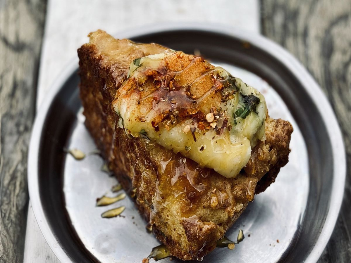 A slice of roasted poblano cornbread, topped with cilantro-lime butter,MFspice blend, and local honey. It sits on a white plate with a black trim