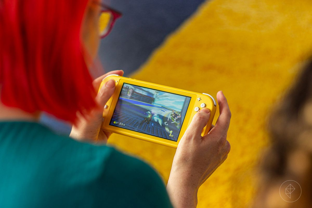 a red-haired woman playing the Nintendo Switch Lite