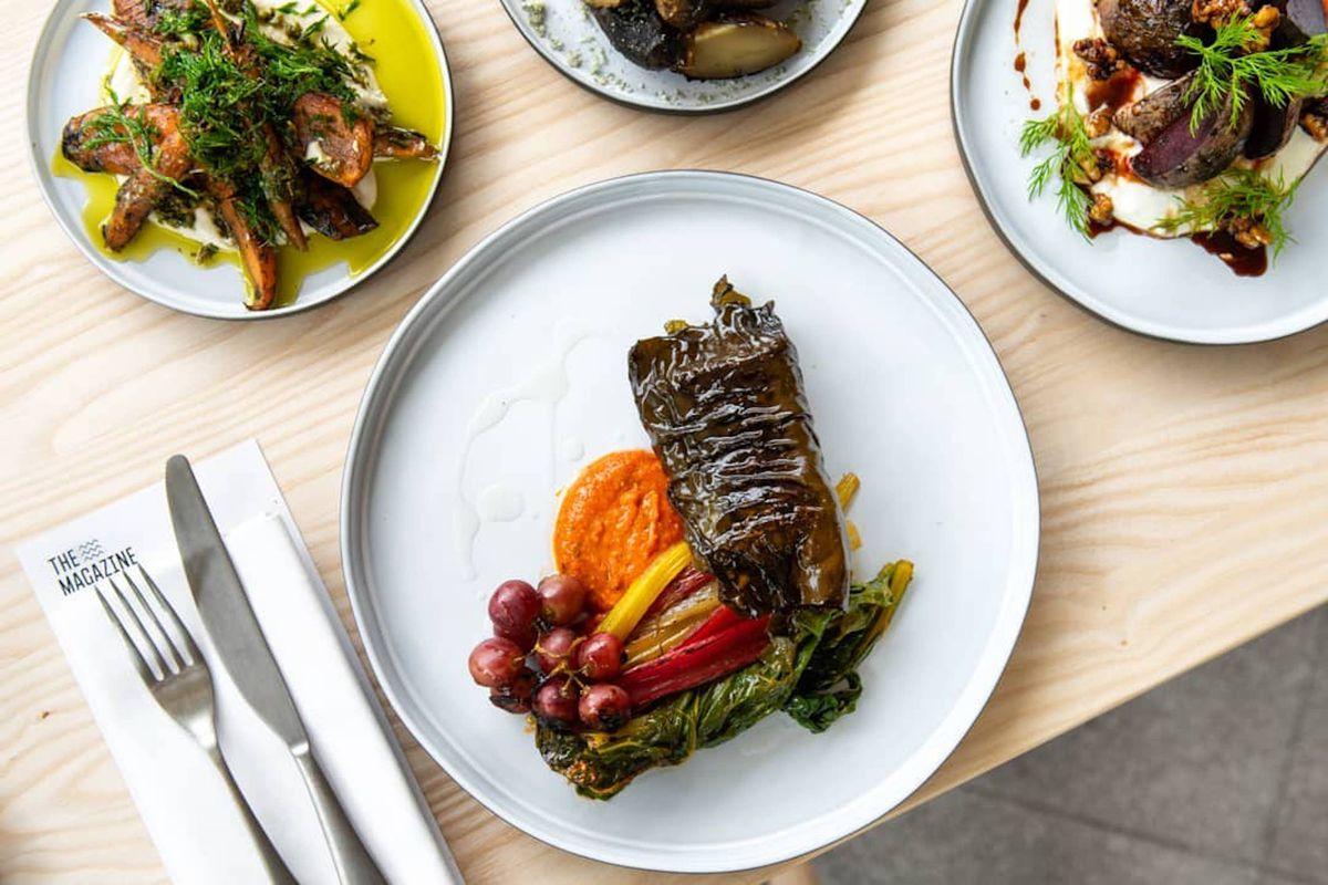 这是海德公园《杂志》菜单上的一盘用海带和甜菜包起来的鱼,放在一个白色盘子上,左手边放着餐具和餐巾。