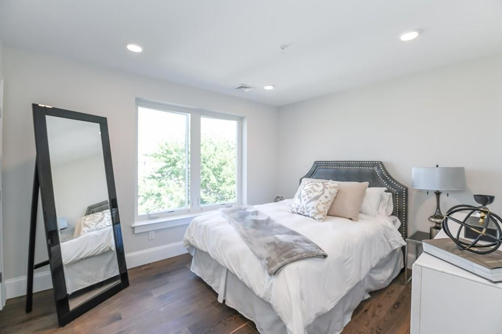 A bedroom with a bed facing a large mirror.