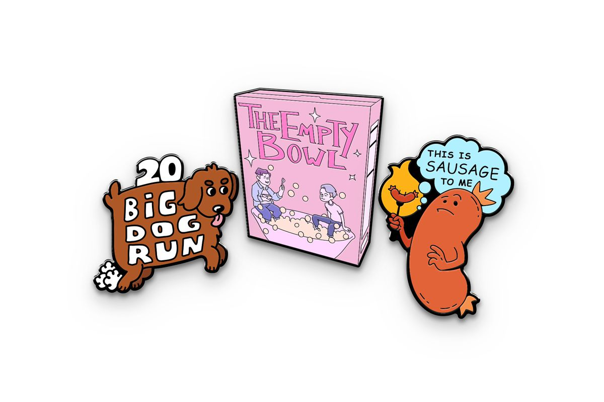 """Image of the three March McElroy merch items. The left image is an enamel pin of a brown dog that says, """"20 Big Dog Run"""" with little clouds coming off its back feet. The center is an enamel pin of a pink cereal box that says, """"The Empty Bowl"""" with an illustration of Justin and Dan Goubert sitting in a cereal bowl. The right image is an enamel pin of a sausage holding a sausage on a fork with a thought bubble that says, """"This is sausage to me."""""""