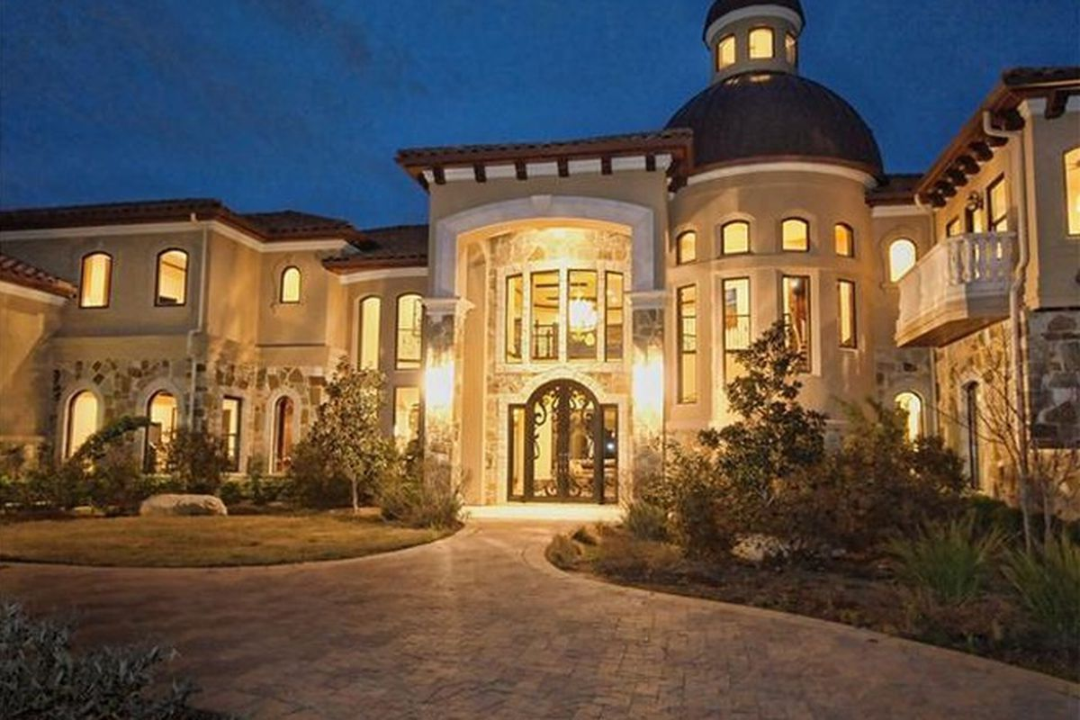 A two-story McMansion aglow at dusk, with turret and two-story entry