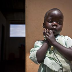 """In this photo taken Friday, April 27, 2012, daughter Betty, 3, stands outside a center set up to help those who have left or fled the Lord's Resistance Army (LRA), where her mother Adye Sunday, 25, works, who was abducted when she was 13 by LRA leader Joseph Kony and forced to be one of his dozens of """"wives"""" and says he's also the father of her two children, in Gulu, Uganda. Adye Sunday isn't sure about the calls to kill or capture LRA leader Joseph Kony, who inspires conflicted thoughts among some people in northern Uganda, despite more than 3,000 children being abducted by the LRA since 2008, according to the U.N. and Human Rights Watch. (AP Photo/Ben Curtis)"""