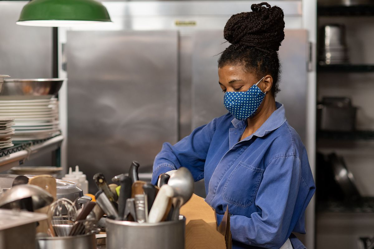 Natalia Pereira among cooking utensils and equipment in a kitchen wearing a blue cloth mask.