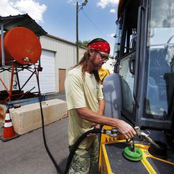 Marc Evans, public properties manager for Woods Cross, fills a backhoe with diesel at the Woods Cross Public Works shop on Tuesday, Aug. 9, 2016.