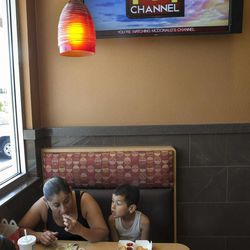 In this photo taken Friday, Sept. 7, 2012, McDonald's patrons Maria Sanchez, 34, and her son Oscar eat at a McDonald's restaurant in Norwalk, Calif. McDonald's is testing its own TV channel in 700 California restaurants in a pilot project that could expand to all the company's restaurants.