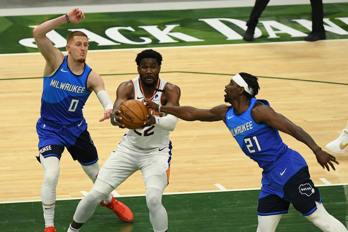 Jrue Holiday of the Milwaukee Bucks knocks the ball away from Deandre Ayton of the Phoenix Suns in the third quarter at Fiserv Forum on April 19, 2021 in Milwaukee, Wisconsin.