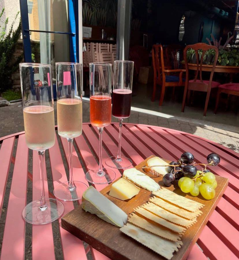 A flight of four sparkling wines rests on a pink wooden table next to a cheese and cracker board.
