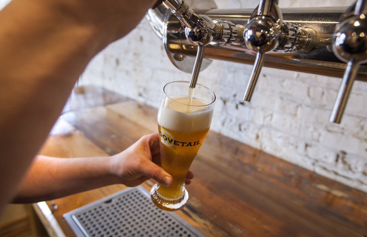 A pint glass being filled with beer under a tap.