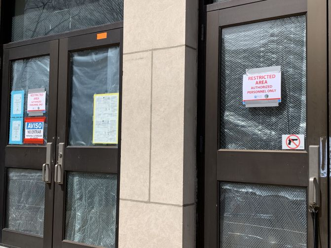 Warning signs are taped to an entrance at Camras Elementary on Wednesday afternoon. | Mitchell Armentrout/Sun-Times