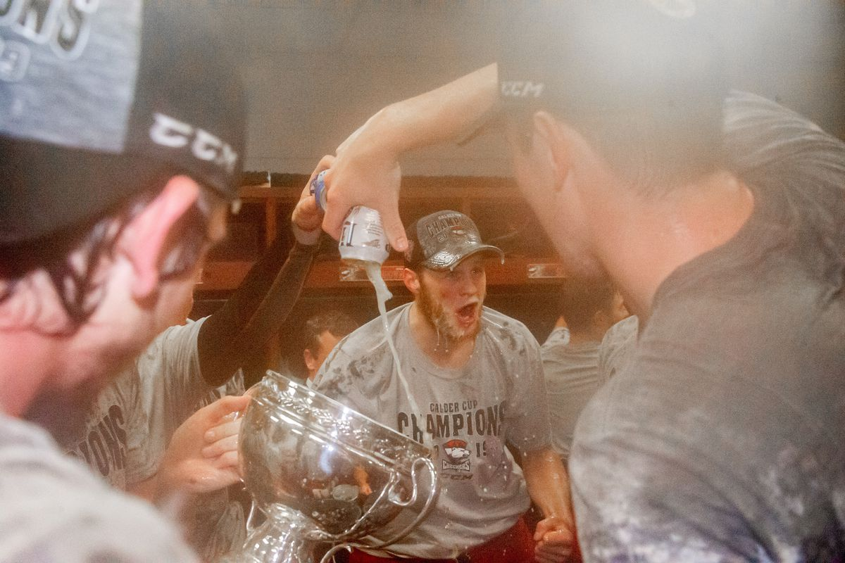 The Charlotte Checkers drink beer out of the Calder Cup trophy and celebrate in the locker room after game five of the AHL Calder Cup Finals against the Chicago Wolves on June 8, 2019, at the Allstate Arena in Rosemont, IL.