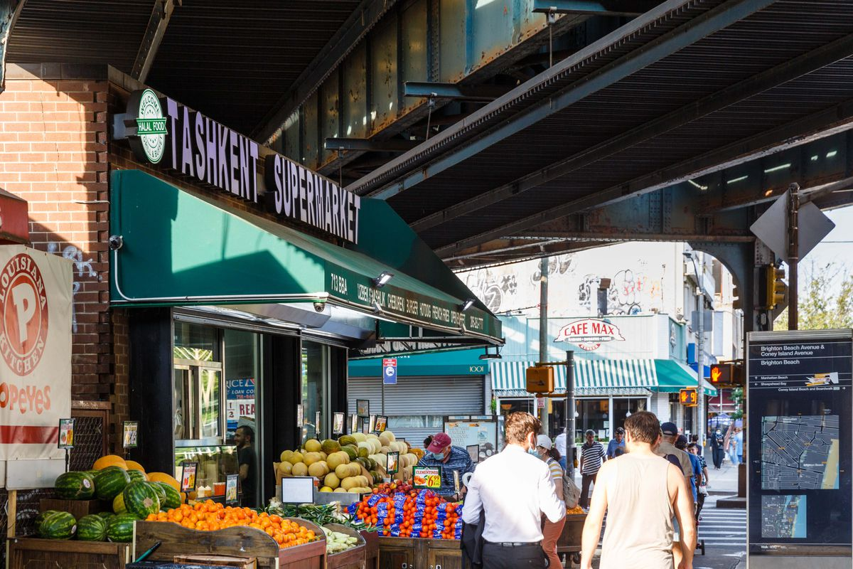 Piles of watermelons, oranges, and other melons sit outside the entrance to Tashkent Supermarket, underneath a green awning