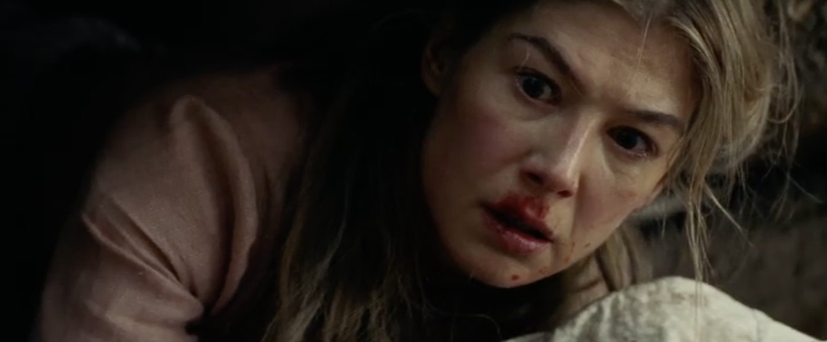 Rosamund Pike with a bloody face hiding in the woods